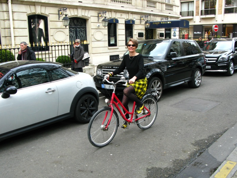 Alice on a red bicycle on the Avenue Montaigne wearing a yellow and black kilt