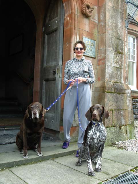 Alice outside the Isle of Ersika Hotel with two dogs wearing Beauchamp of London collars and leads