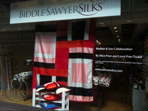 picture of a silk quilt and cushions made by Alice & Co for Biddle Sawyer Silks window display in Berwick Street Soh London