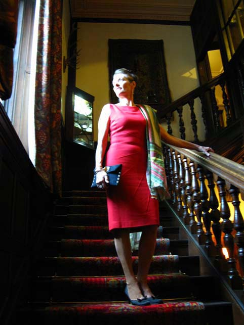 Alice in a red wool crepe madame tra la la dress on the staircase of the Isle of Eriska Hotel